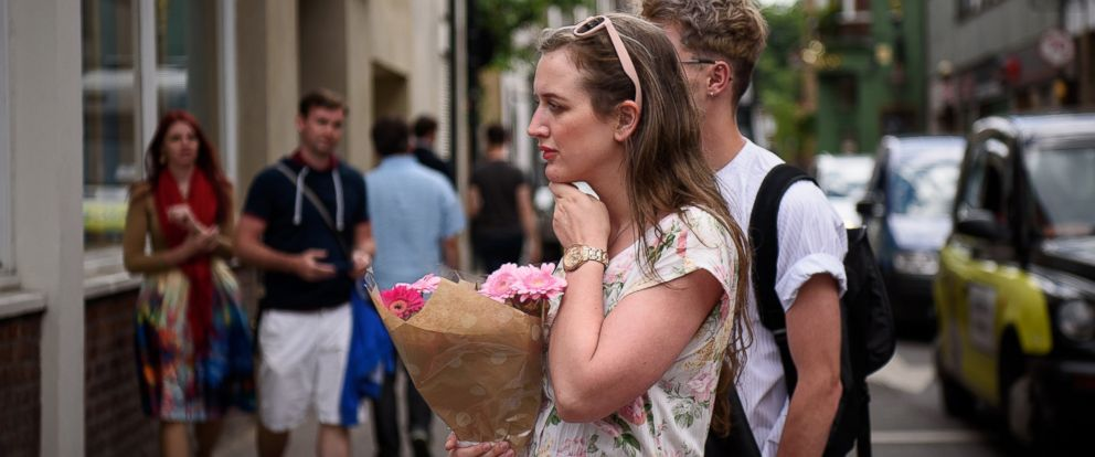 PHOTO: A woman prepares to lay some flowers for those killed, at the perimeter cordon, following last nights London terror attack, June 4, 2017 in London, England.