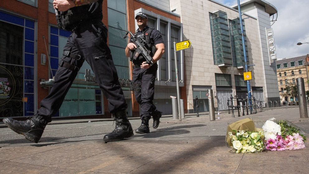 Armed police patrol Shudehill as they walk past floral tributes to victims, May 23, 2017, in Manchester, England.