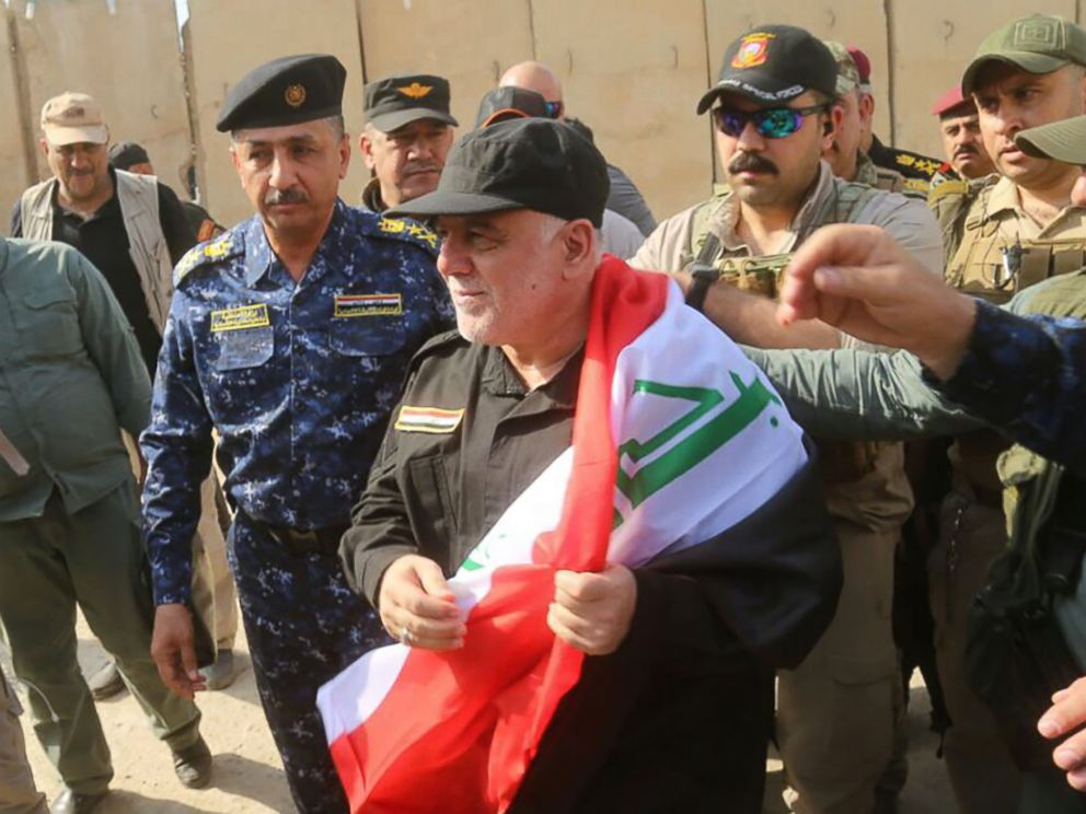 PHOTO: A handout picture released by the Iraqi Federal Police on July 9, 2017, shows Iraqi Prime Minister Haider al-Abadi wrapped in the Iraqi national flag while walking alongside police and army officers upon his arrival in Mosul.