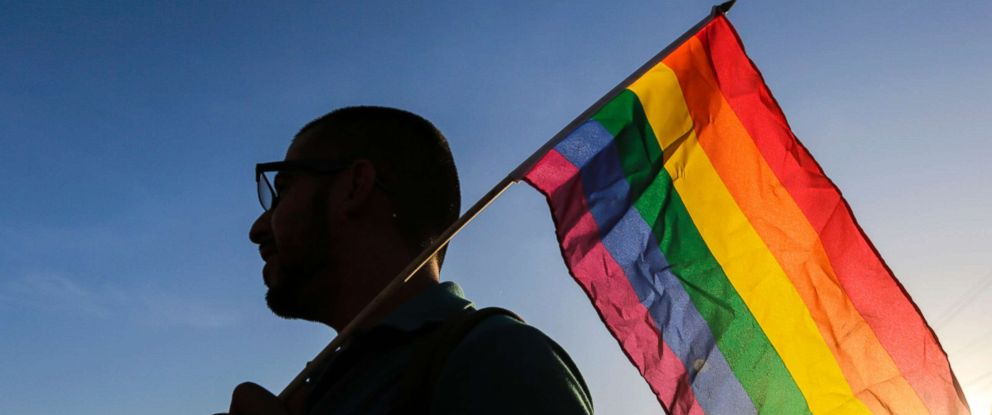 PHOTO: An LGBT community member and supporter holds up a rainbow flag.