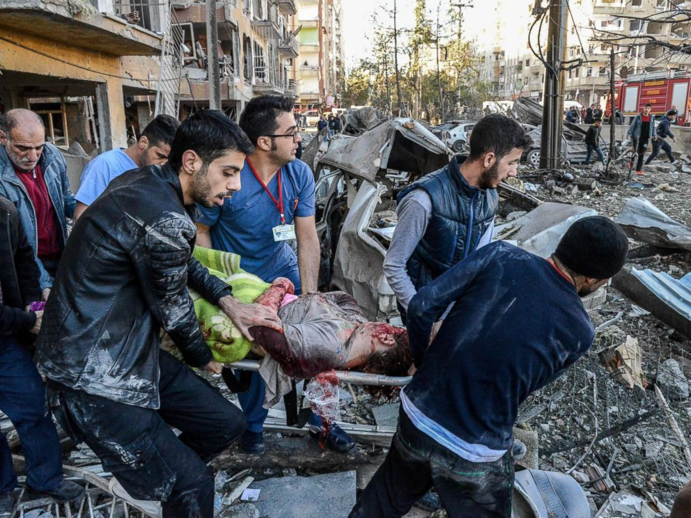PHOTO: Rescue officials and people carry an injured man at the explosion site, Nov. 4, 2016, after a strong blast in the southeastern Turkish city of Diyarbakir.