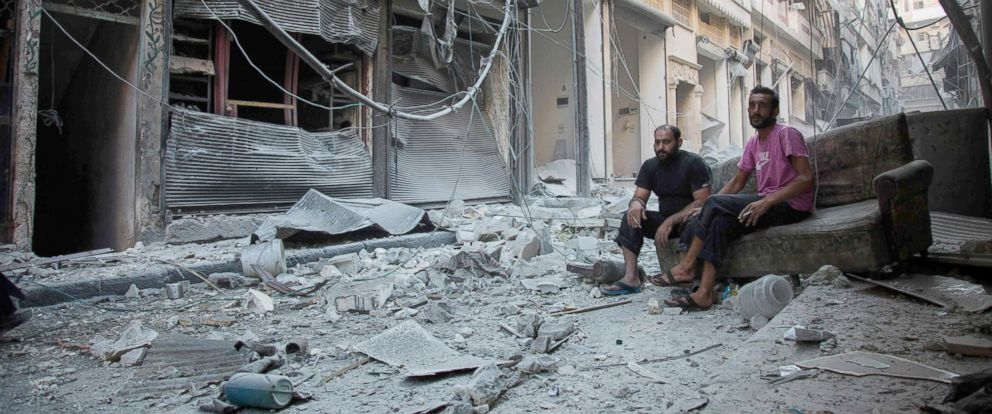 PHOTO: Syrians sit and look at the rubble following an airstrike on the regime-controlled neighborhood of Karm al-Jabal, on Sept. 18, 2016.