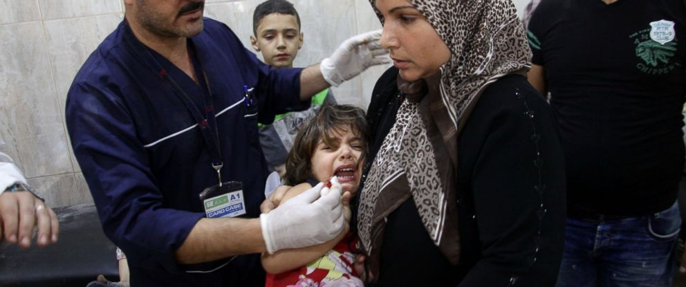 PHOTO: A Syrian woman brings a child to al-Razi hospital, on Oct. 16, 2016, in the government-controlled district of the al-Jamiliyeh in Aleppo, following shells on al-Sayed Ali neighborhood.