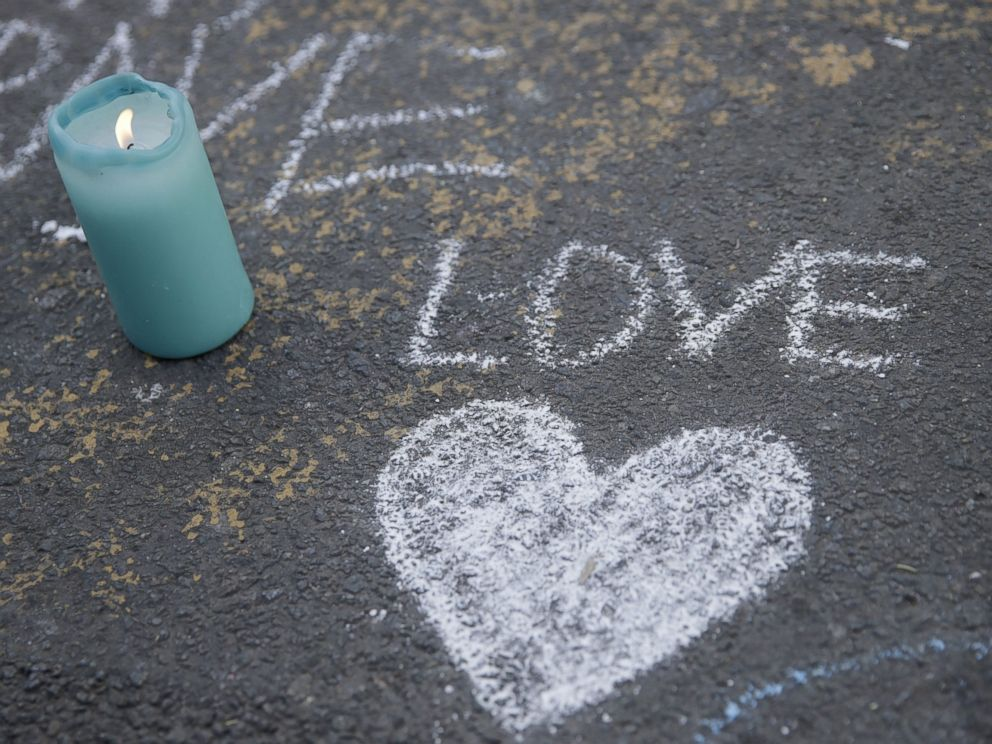 PHOTO: A candle burns next to a heart drawing at a makeshift memorial at Place de la Bourse following attacks in Brussels, March 22, 2016.