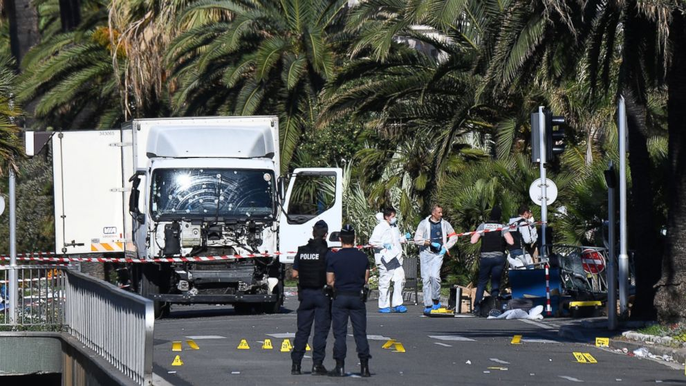 Forensics officers and policemen look for evidence near a truck on the Promenade des Anglais seafront in the French Riviera town of Nice on July 15, 2016, after it drove into a crowd watching a fireworks display.