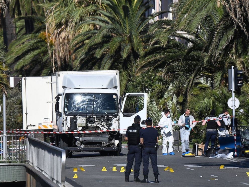 PHOTO: Forensics officers and policemen look for evidence near a truck on the Promenade des Anglais seafront in the French Riviera town of Nice on July 15, 2016, after it drove into a crowd watching a fireworks display.