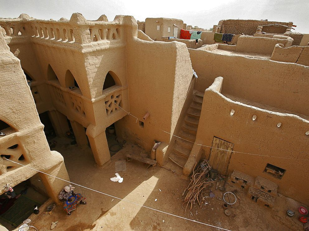 Wonderful PHOTO: A Woman Rests In The Courtyard Of A Large Earthen Mud House, In