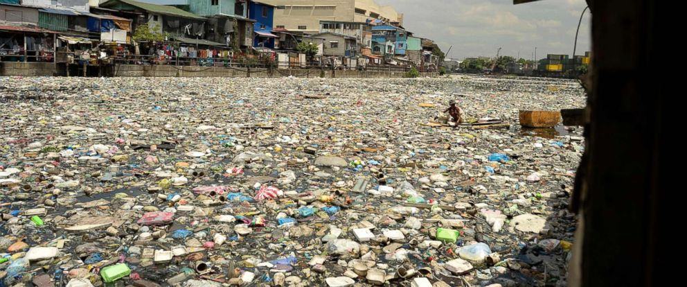 PHOTO: Teresita Gapayao, 51, a scavenger for 12 years, wades through garbage using a makeshift raft made from styrofoam on the Estero de Vitas tiver in Tondo, Manila on April 21, 2016.
