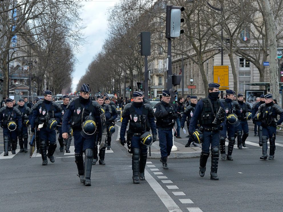 PHOTO: French riot police walk in front of protestors during the demonstration against labour reforms on March 9, 2016 in Paris, France.