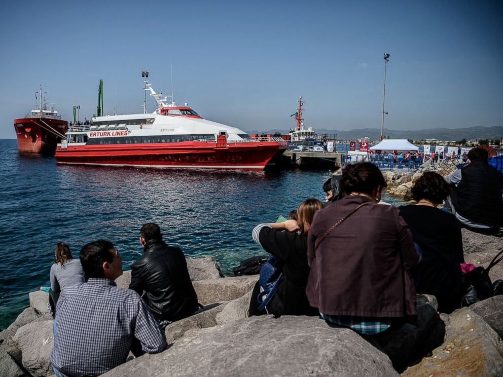 PHOTO: People gather on the beach as migrants deported from Greece arrive aboard a small Turkish ferry in the port of Dikili district in Izmir, Turkey, on April 4, 2016.