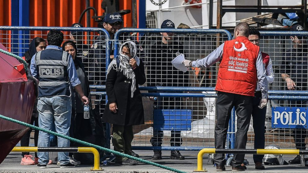 A Turkish police officer escorts deported women migrants from a small Turkish ferry carrying migrants who are deported to Turkey on April 4, 2016 as they arrive at the port of Dikili district in Izmir.
