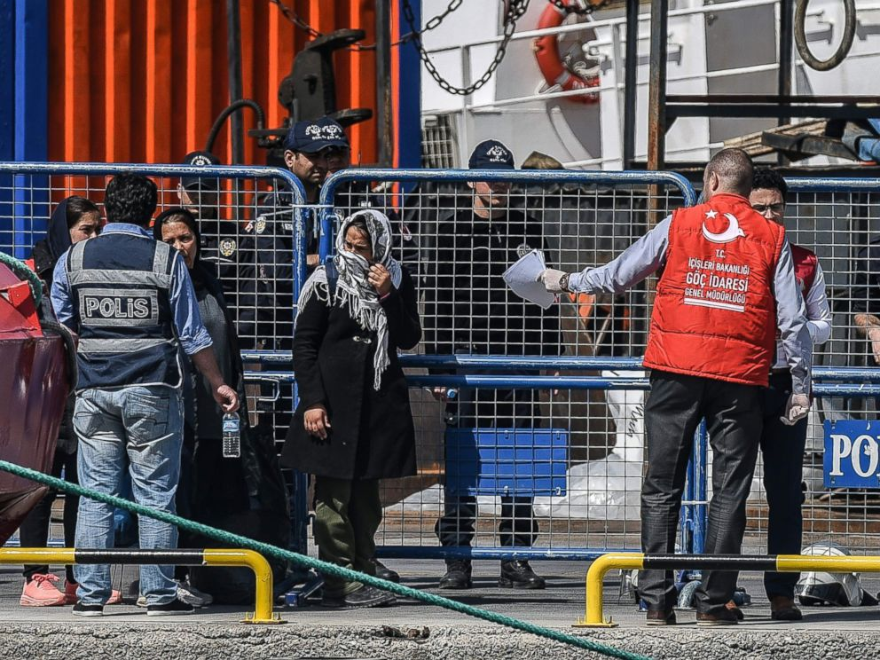 PHOTO: A Turkish police officer escorts deported women migrants from a small Turkish ferry carrying migrants who are deported to Turkey on April 4, 2016 as they arrive at the port of Dikili district in Izmir.