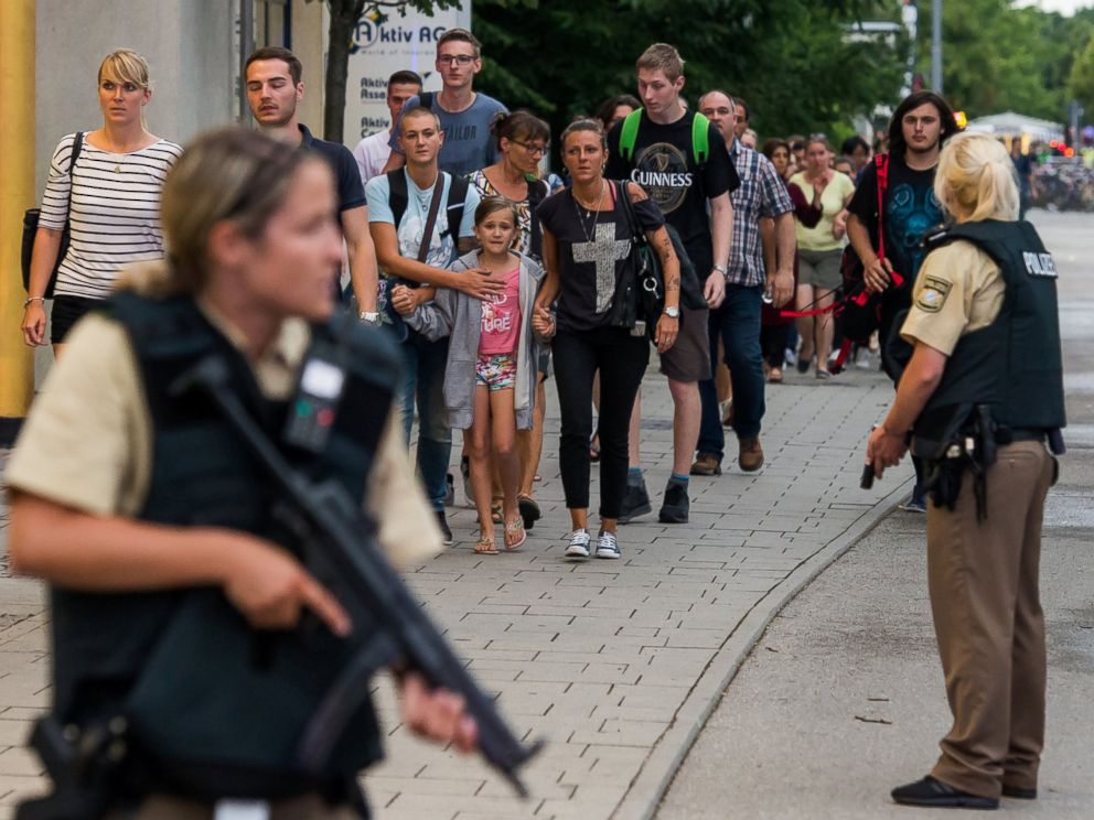 PHOTO: Police officers escort people from inside the shopping center as they respond to a shooting at the Olympia Einkaufzentrum on July 22, 2016 in Munich.