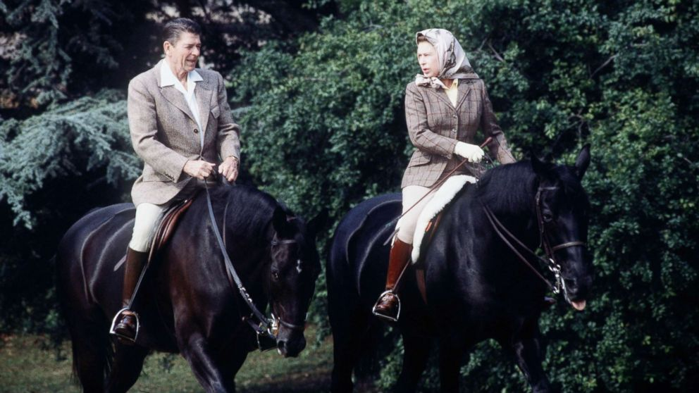 The queen rides with President Ronald Reagan on the grounds of Windsor Castle during his state visit on June 8, 1982.