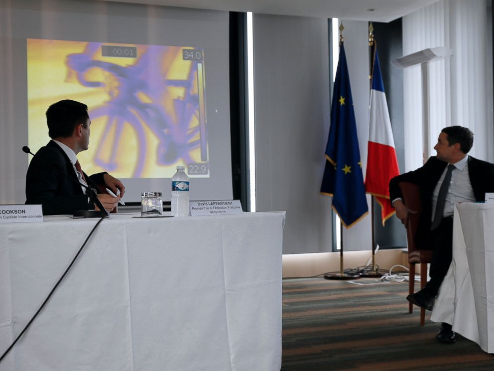 PHOTO: President of the French cycling federation David Lappartient (L) and French Minister for Higher Education and Research Thierry Mandon (R) look at a screen during a press conference on mechanical fraud, on June 27, 2016.