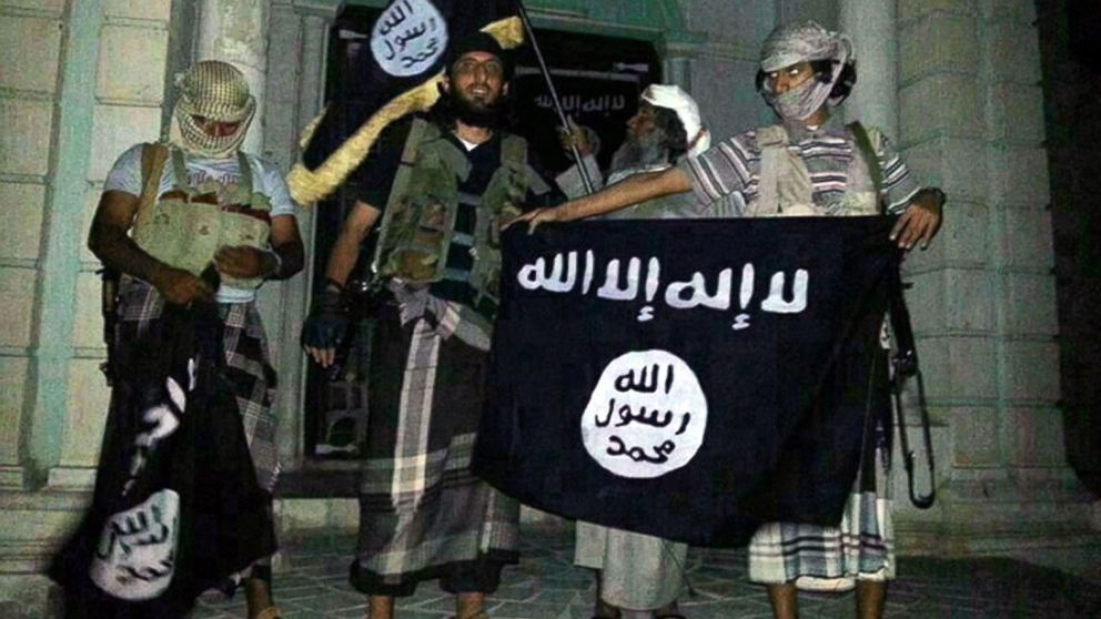 A picture taken with a mobile phone early on May 24, 2014 shows Al-Qaeda militants posing with Al-Qaeda flags in front of a museum in Seiyun, second Yemeni city of Hadramawt province, after launching a massive pre-dawn assault that killed at least 15 soldiers and police.