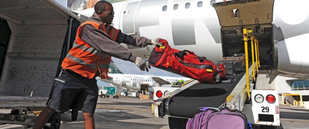 PHOTO: A baggage handler loads a plane at Denver International Airport.