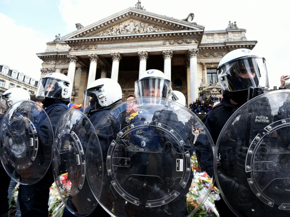 PHOTO: Riot police stand guard as far-right football hooligans disturb the peaceful rally outside the stock exchange, Place de la Bourse square in Brussels, March 27, 2016.