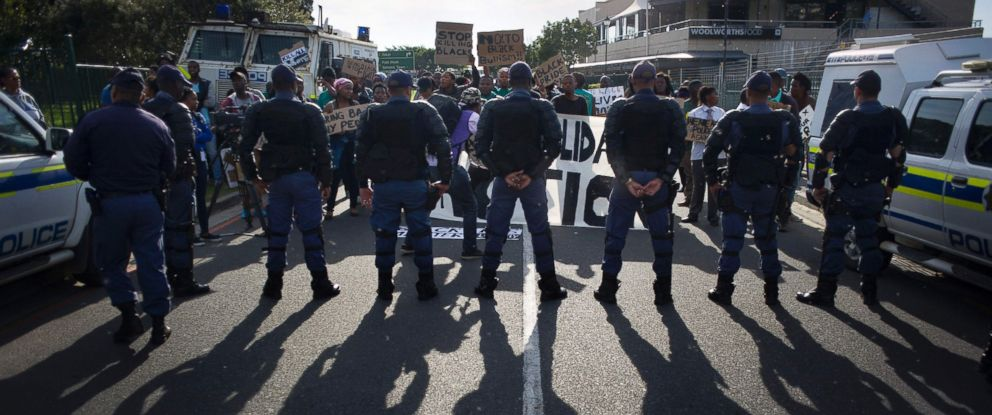 PHOTO: South African police officers block members of the Black Solidarity Action group to march towards the US consulate, to denounce the killing of black Americans in the United States, in Cape Town, July 13, 2016.