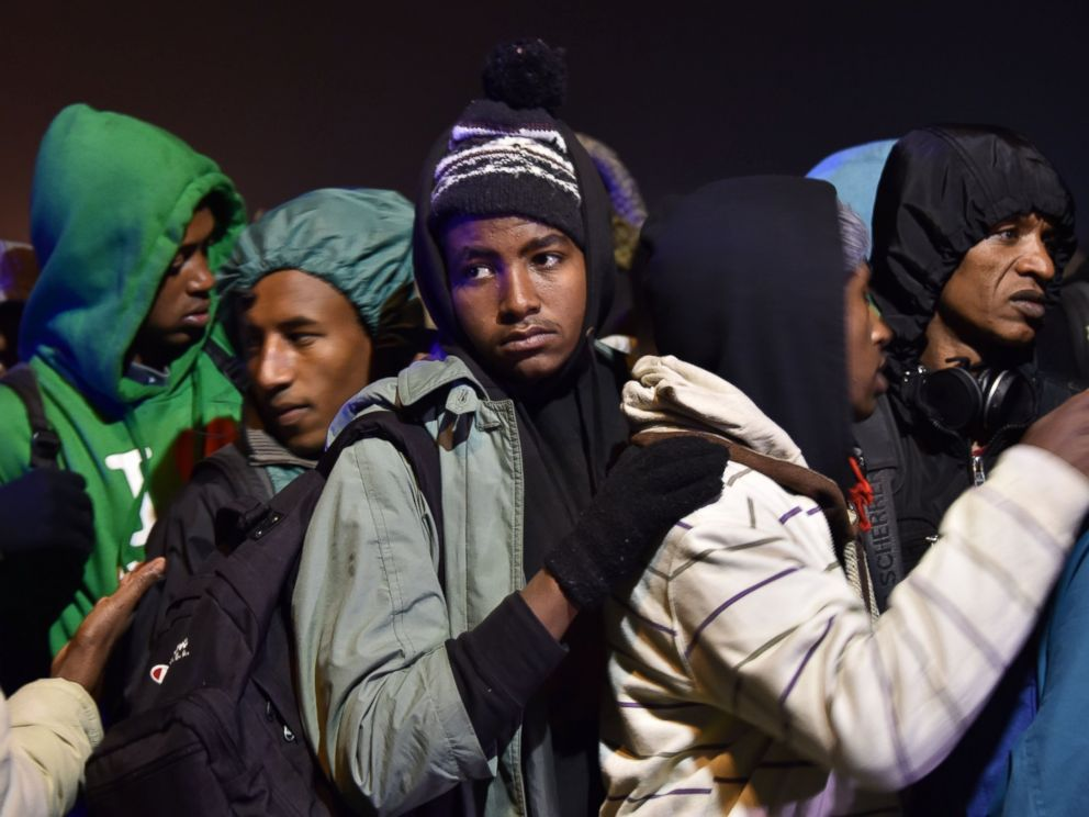 PHOTO: Migrants line up for transportation by bus to reception centers across France, from the Jungle migrant camp in Calais, northern France, Oct. 24, 2016.