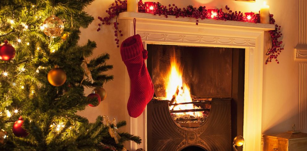PHOTO: Christmas tree and stocking near fireplace.