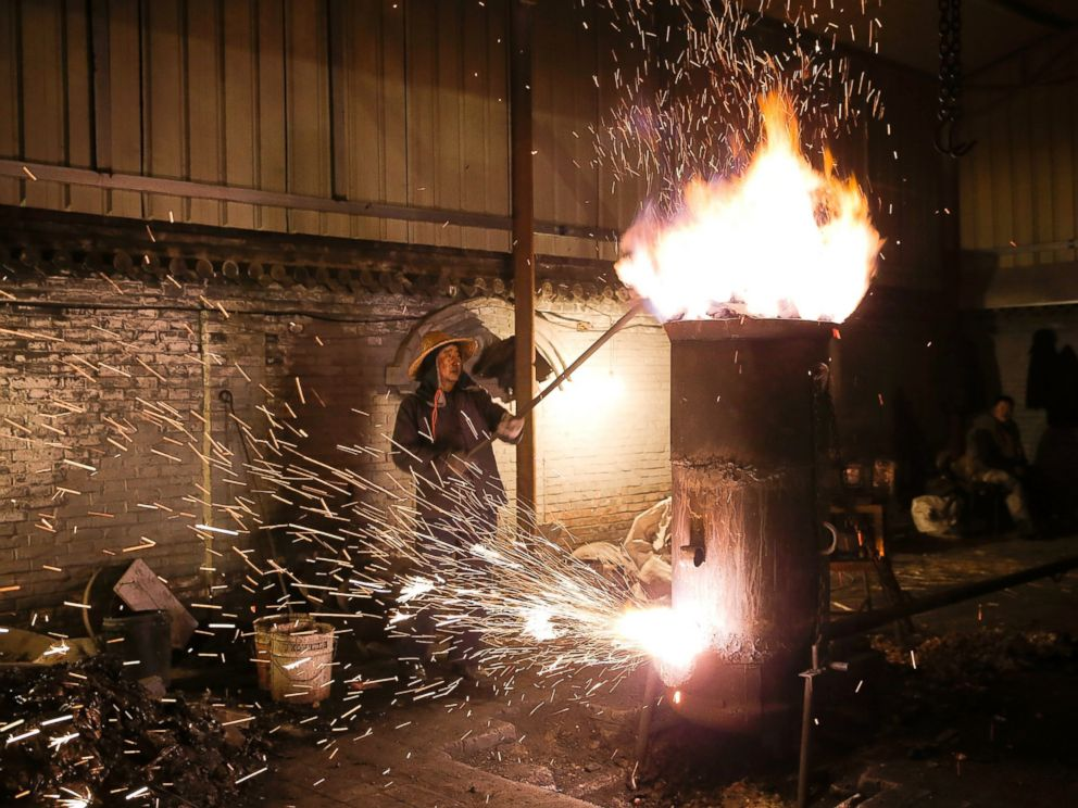 PHOTO: The throwing of ladles full of molten iron against brick walls creates a shower of sparks that looks like fireworks, Feb. 23, 2016, in Nuanquan, Hebei Province, China.