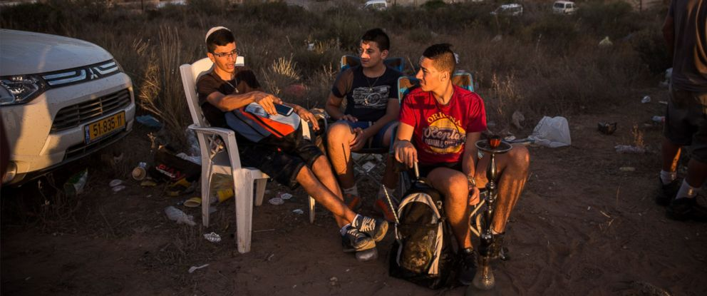 "PHOTO: Civilians and members of the media wait to see Israeli attacks inside Gaza from the top of a hill on the sixth day of Israels operation ""Protective Edge"" on July 13, 2014 in Sderot, Israel."