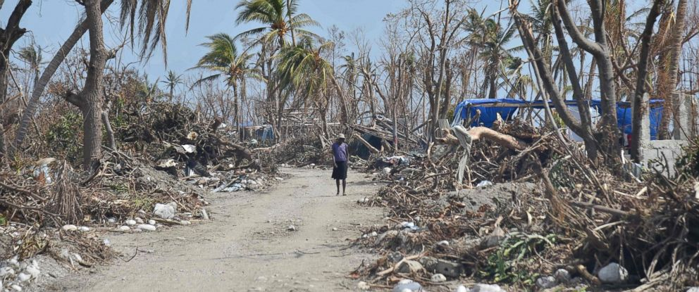 PHOTO: A woman walks in the street of Les Cayes, Haiti, Oct.10, 2016, following the passage of Hurricane Matthew.