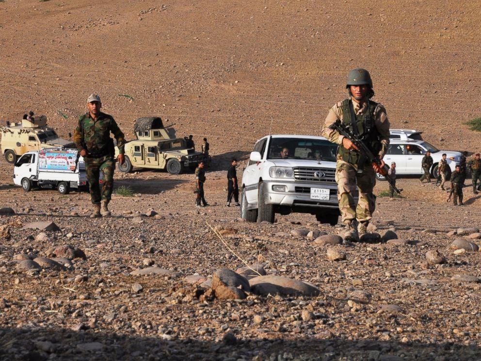 PHOTO: Members of the Kurdish Peshmerga forces take a position to fight
