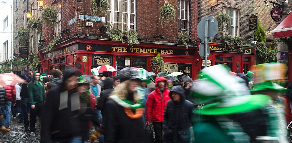 PHOTO: Pedestrians carrying umbrellas and wearing St. Patricks day hats and scarves move past the Temple Bar public house in Dublin, Ireland, March 17, 2013.