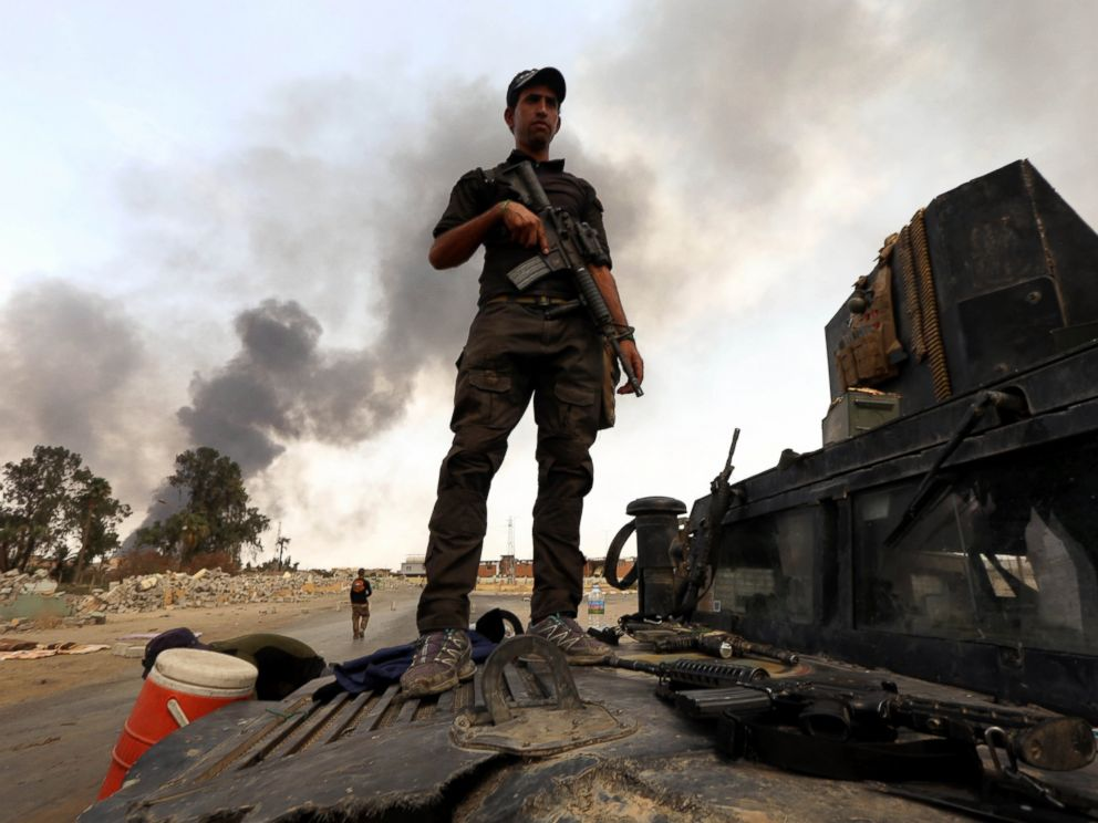 PHOTO: A member of the Iraqi government forces stands on a military vehicle as smoke billows from oil wells, set ablaze by Islamic State (IS) group militants before fleeing the oil-producing region of Qayyarah, Aug. 30, 2016.