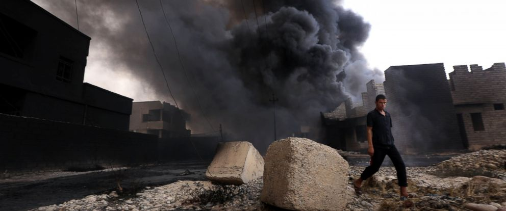 PHOTO: An Iraqi man walks near smoke billowing from oil wells, set ablaze by Islamic State (IS) group militants before fleeing the oil-producing region of Qayyarah, Aug. 30, 2016.