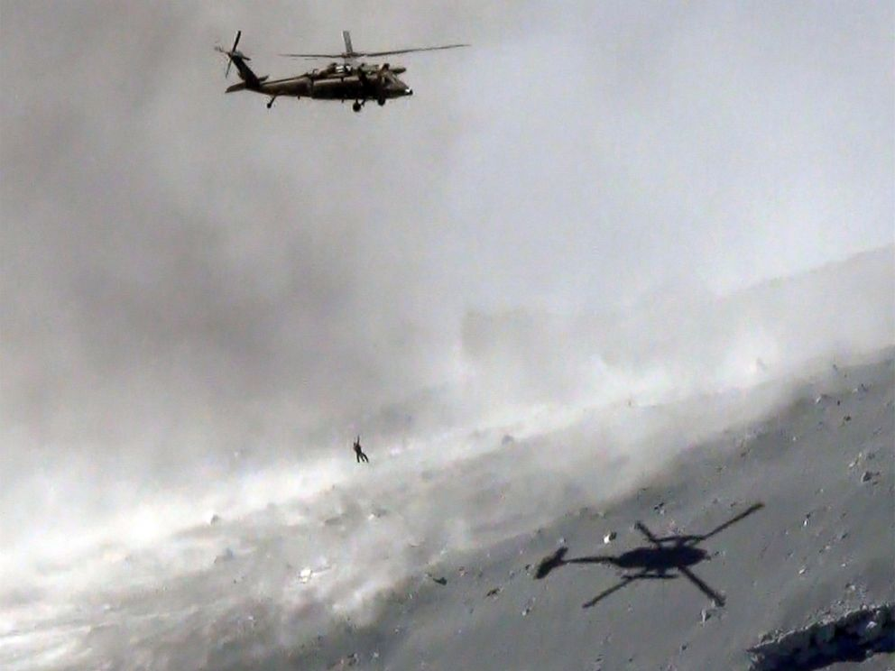 PHOTO: This aerial picture taken on September 28, 2014 shows a helicopter of Japans Self Defense Force lifting a survivor from volcanic ash covered top of Mount Ontake at Nagano prefecture. (Photo credit JIJI PRESS/AFP/Getty Images)