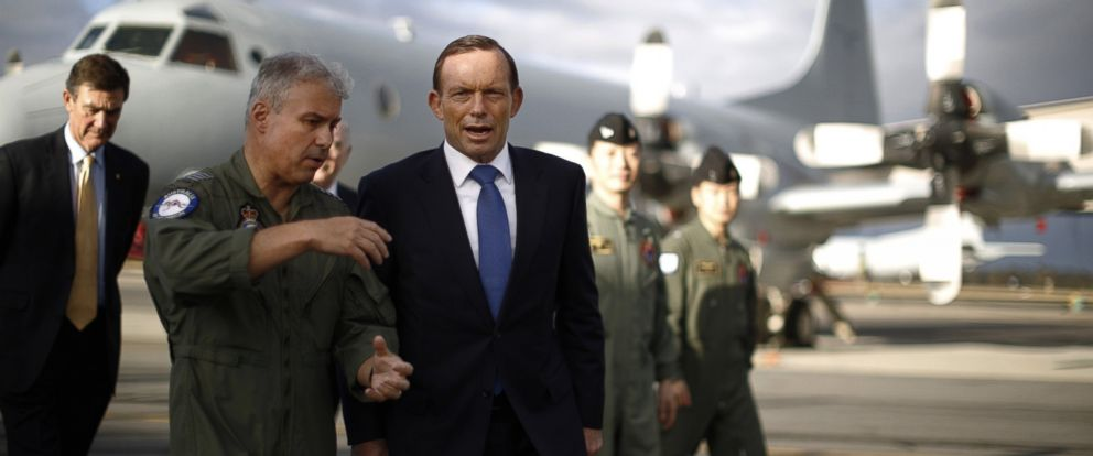 PHOTO: Australian Prime Minister Tony Abbott, center, is guided around a Royal Australian Air Force P-3C Orion aircraft by Australian Air Force Group Commander Craig Heap, second from left.