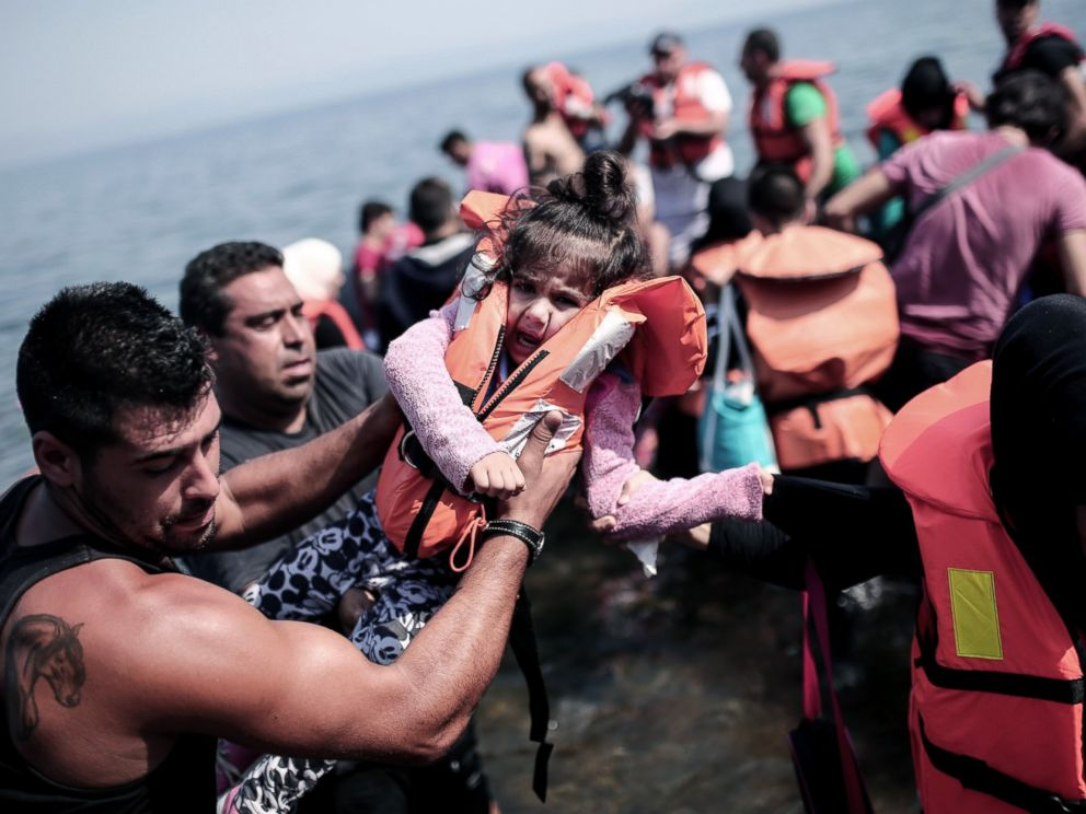 PHOTO: A refugee carries a child as they arrive on the shores of the Greek island Lesbos in an inflatable dingy across the Aegean Sea from from Turkey, Sept. 3, 2015.