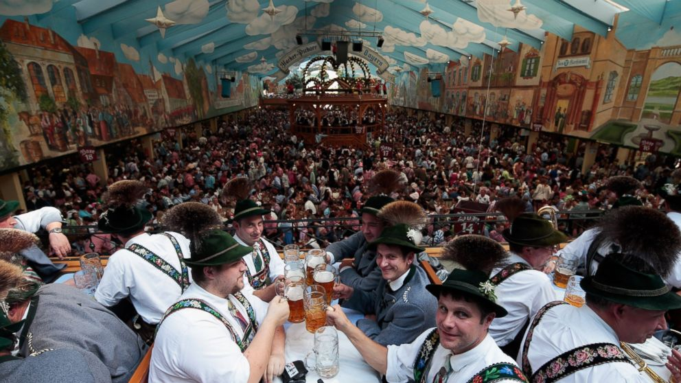 Visitors wearing traditional Bavarian clothes clink beer glasses in the Hacker-Pschorr tent at the Oktoberfest 2013 beer festival in Munich, Germany Sept. 22, 2013.