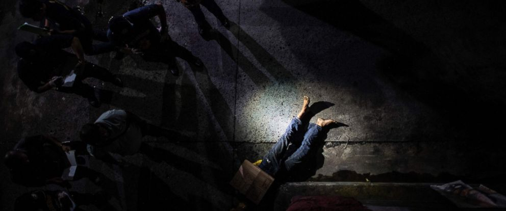 PHOTO: Police officers investigating the dead body of an alleged drug dealer in Manila, Philippines, July 8, 2016.
