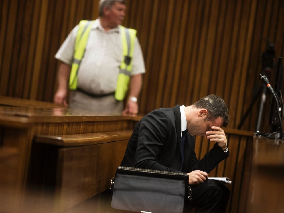 PHOTO: Oscar Pistorius looks at his notes during the fourth day of his trial for the murder of his girlfriend Reeva Steenkamp at the North Gauteng High Court in Pretoria, March 6, 2014.
