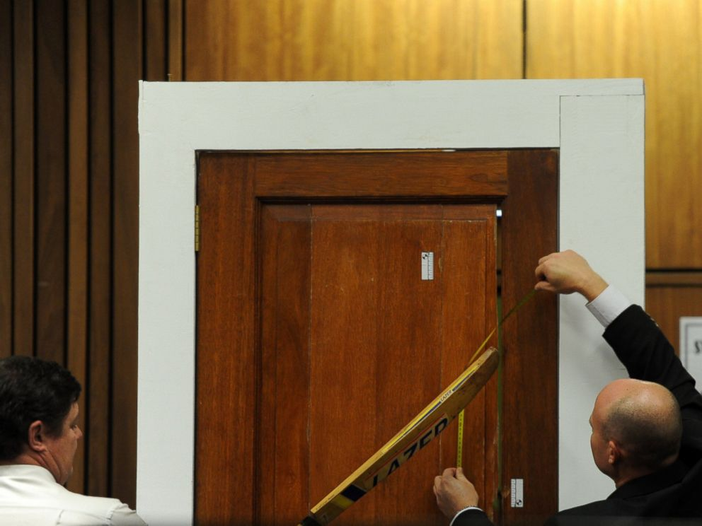 PHOTO: Forensic investigator Johannes Vermeulen, left, takes part in the reconstruction of hitting a door with a cricket bat during the trial of Oscar Pistorius in Pretoria, South Africa on March 12, 2014.