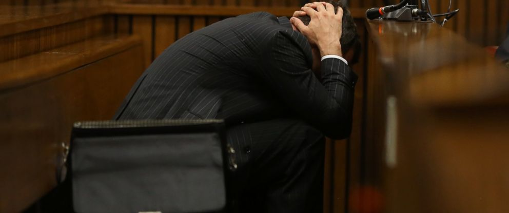 PHOTO: Olympic and Paralympic track star Oscar Pistorius leans over a container during a hearing
