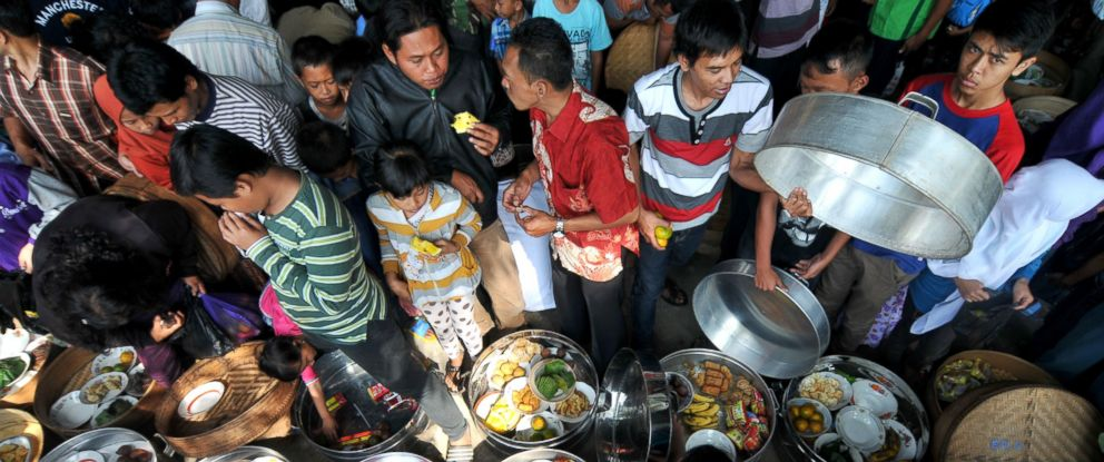 PHOTO: Indonesian muslims eat together after praying during Javanese ritual called Nyadran at Purwoloyo Cemetery in Boyolali, Central Java, Indonesia, June 15, 2014.