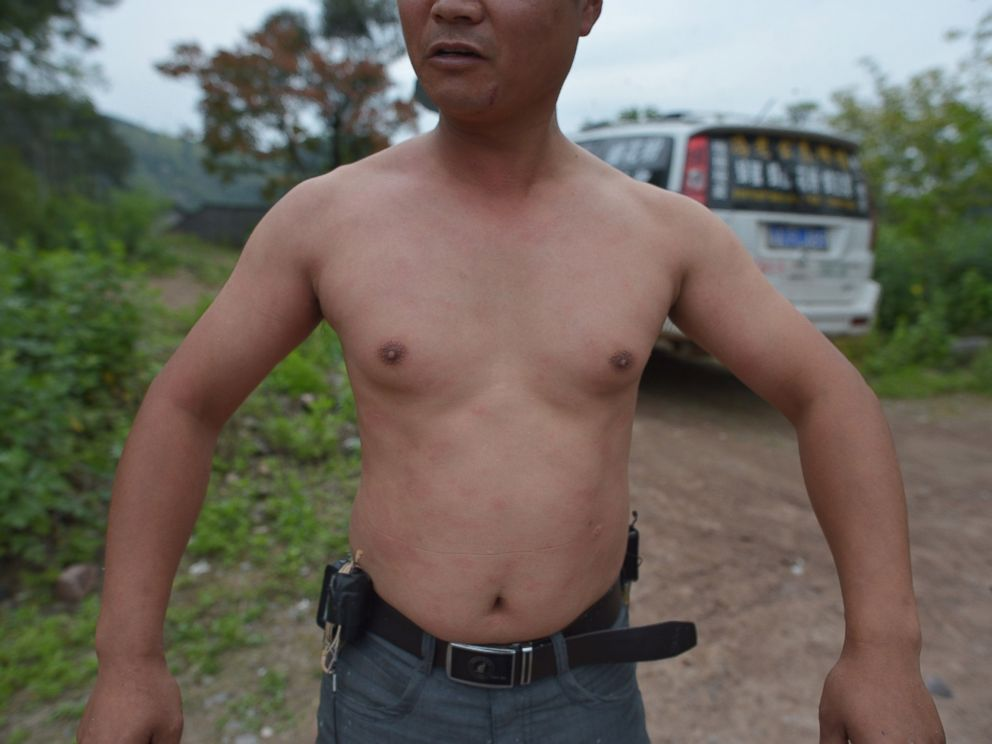 PHOTO: This picture taken on April 9, 2014 shows She Ping, a 34 year-old local beekeeper, showing his body after wearing bees on a small hill in southwest Chinas Chongqing.