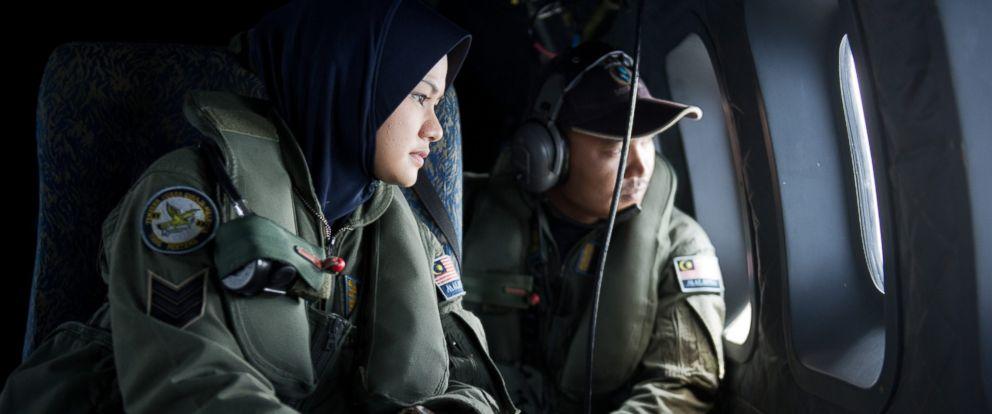 PHOTO: Crew members look outside the windows of a Malaysian Air Force CN235 aircraft