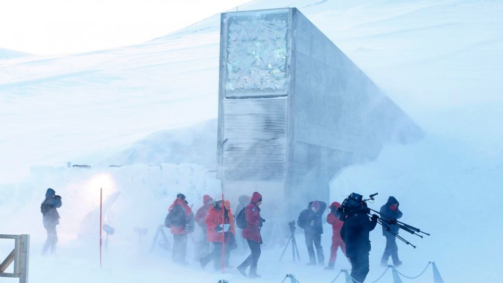 Journalists and cameramen walk under a gust of cold wind near the entrance of the Svalbard Global Seed Vault that was officially opened near Longyearbyen, Norway in this Feb. 26, 2008 file photo.
