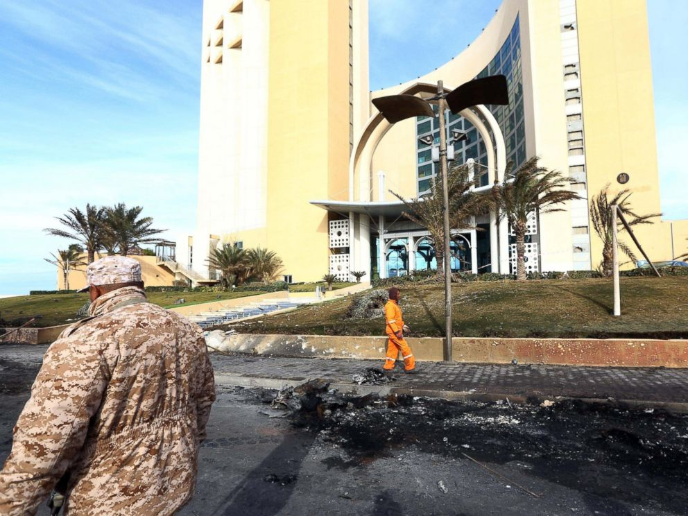 PHOTO: A member of security, left, for Tripolis central Corinthia Hotel looks on as sanitation workers clean the debris outside the hotel on Jan. 28, 2014.