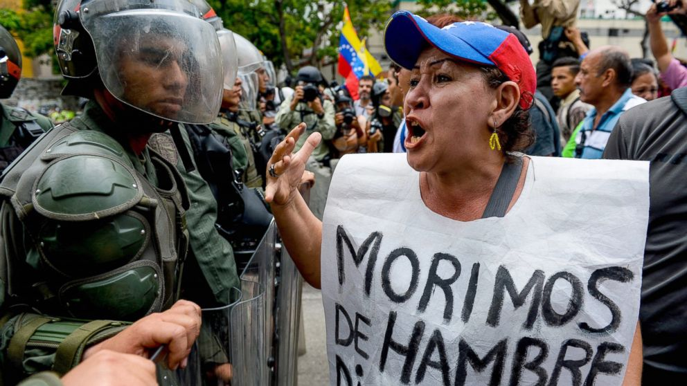 "A woman with a sign reading ""We starve"" protests against new emergency powers decreed this week by President Nicolas Maduro in front of a line of riot policemen in Caracas, May 18, 2016."