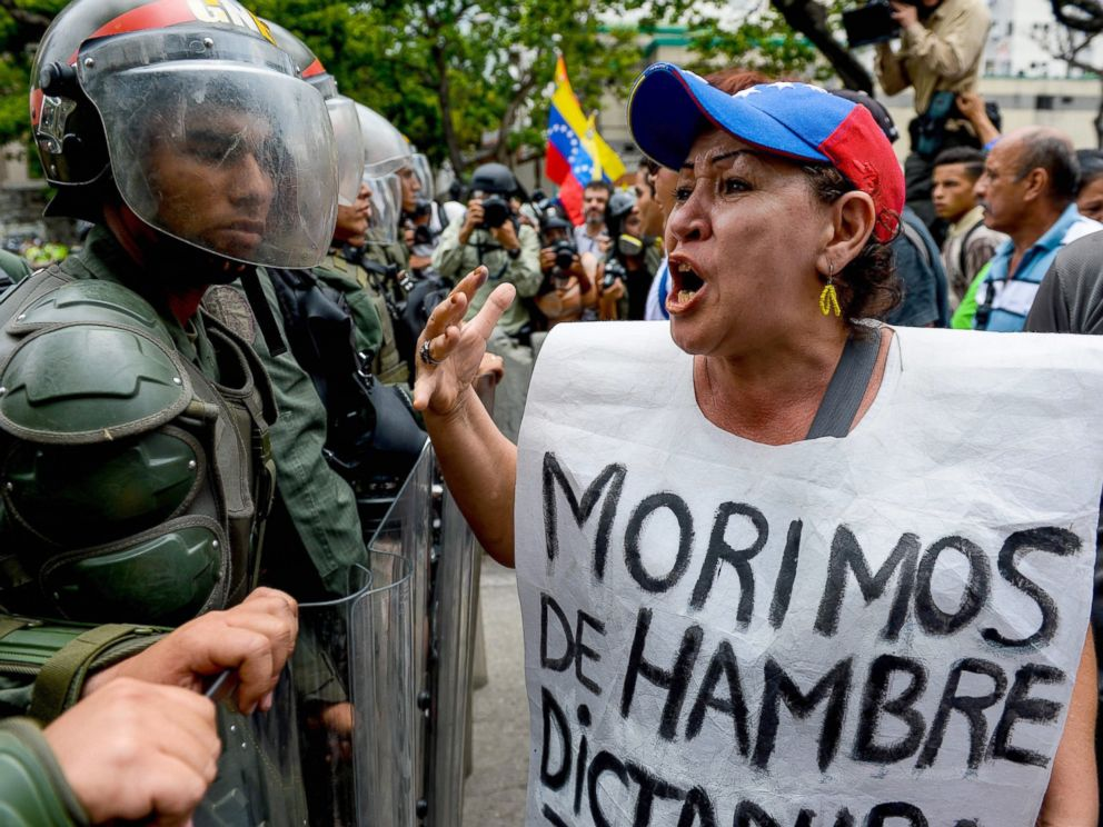 PHOTO: A woman with a sign reading We starve protests against new emergency powers decreed this week by President Nicolas Maduro in front of a line of riot policemen in Caracas, May 18, 2016.