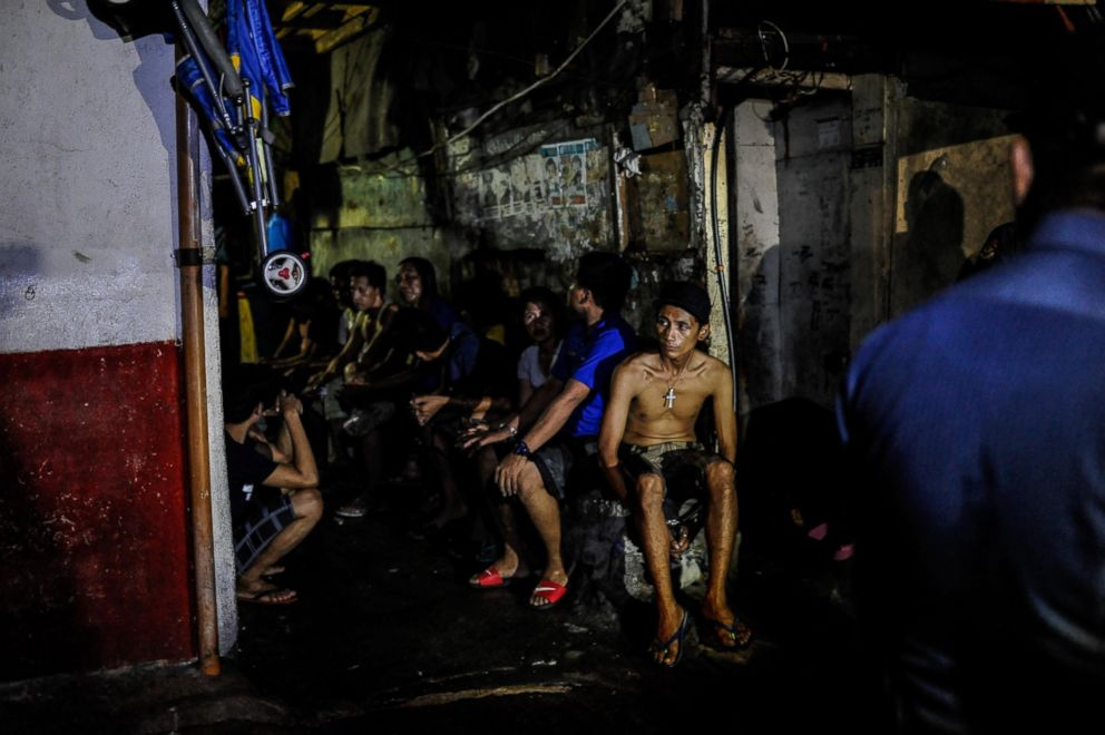 Suspected drug users and drug dealers are arrested by police during a nighttime raid on a suspected drug den, June 16, 2016, in Manila, Philippines.