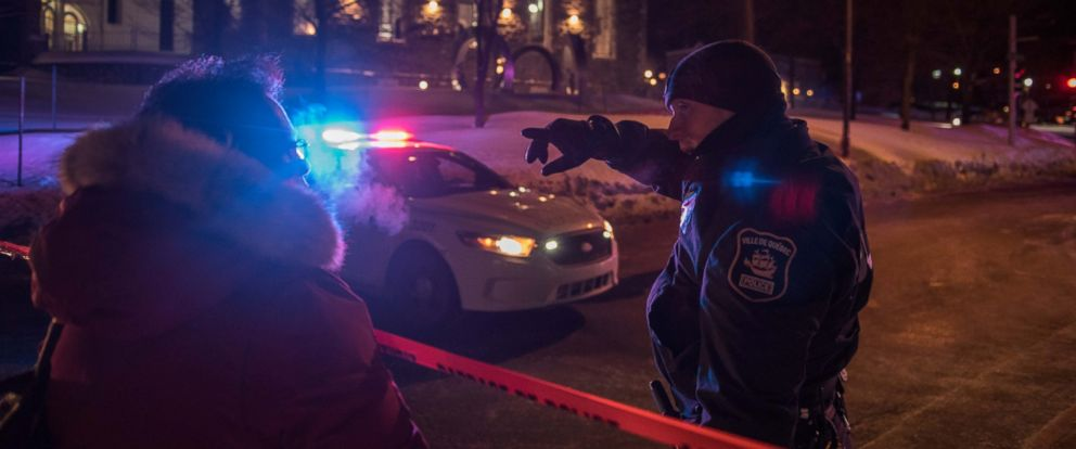 PHOTO: A Canadian police officer talks to a woman after a shooting in a mosque at the Quebec City Islamic cultural center on Sainte-Foy Street in Quebec city on January 29, 2017.