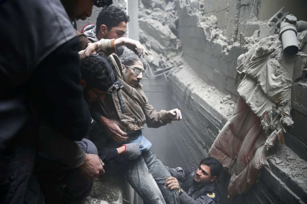 PHOTO: Civil defense help a man from a shelter in the besieged town of Douma in eastern Ghouta in Damascus, Syria, on Feb. 22, 2018.